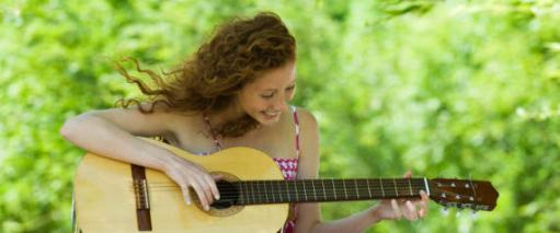 Young woman playing acoustic guitar outdoors